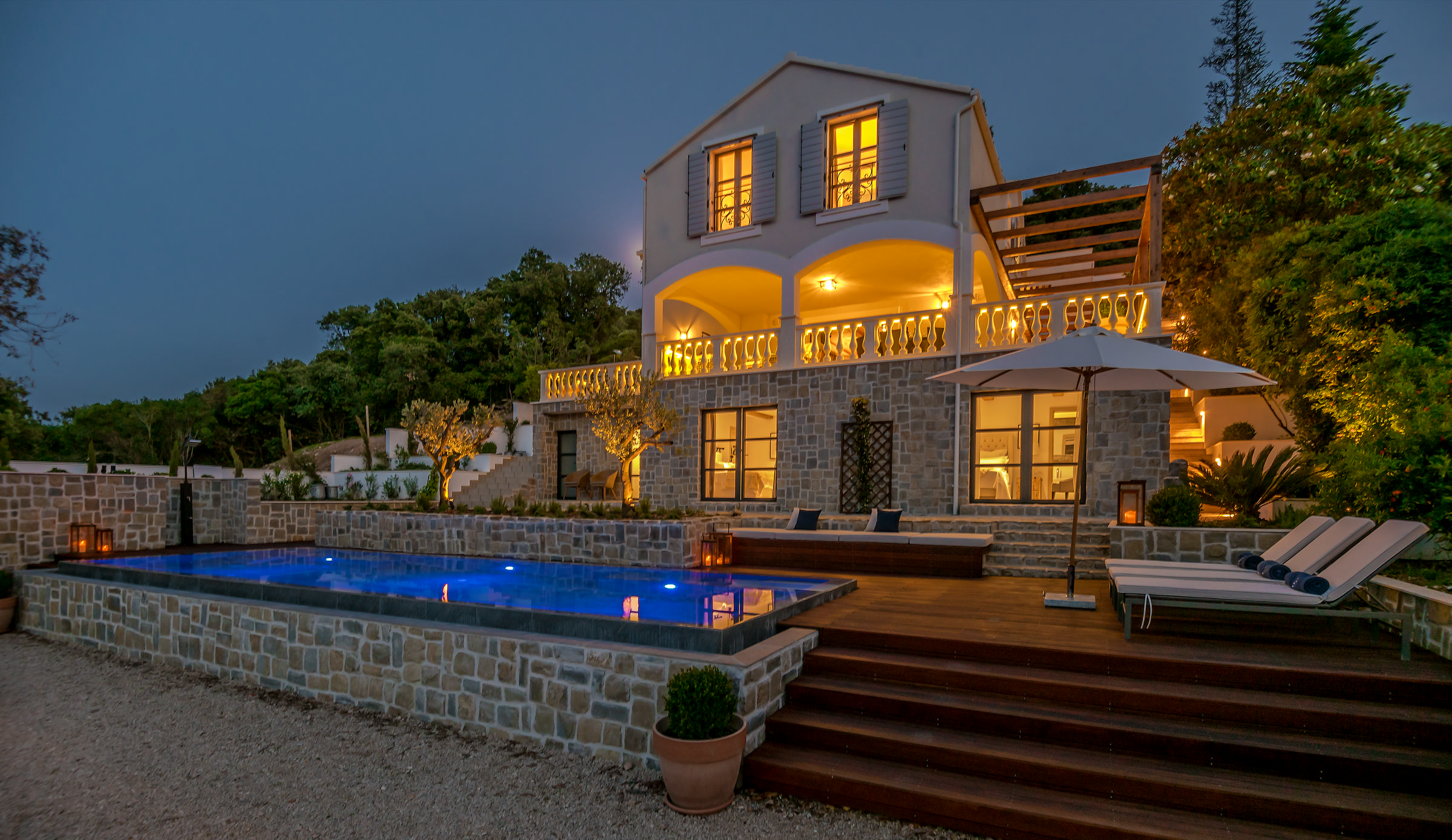 The night image of a residence with a pool with strong yellow light.