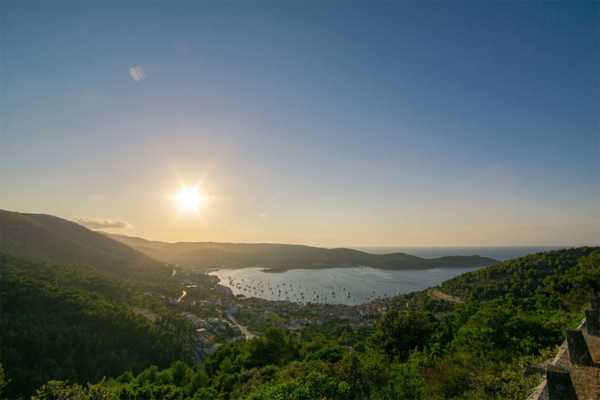 The suns sets over the small bay. The bay is full of yachts and small boats.