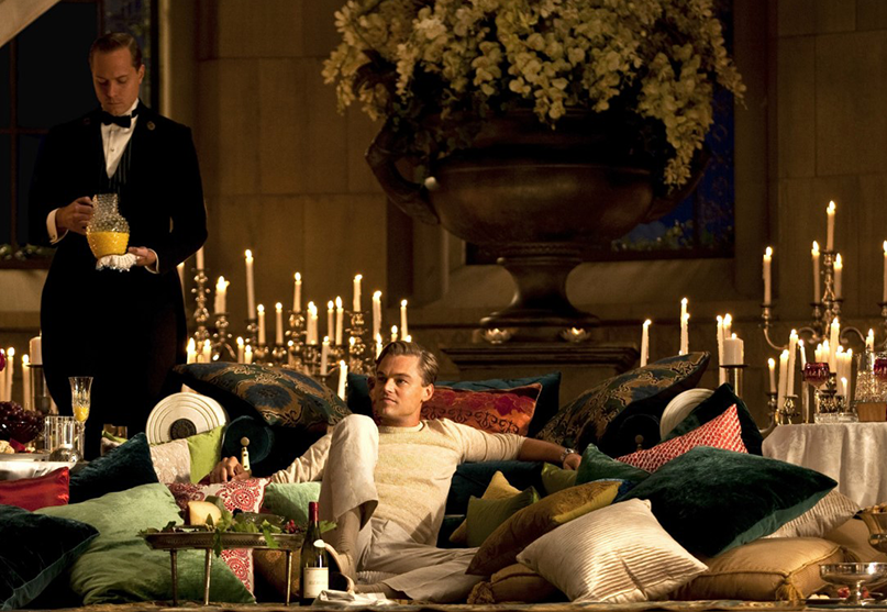 Actor Leonardo Di Caprio sitting on the wooden floor surrounded by pillows on the set of the movie The Great Gatsby.