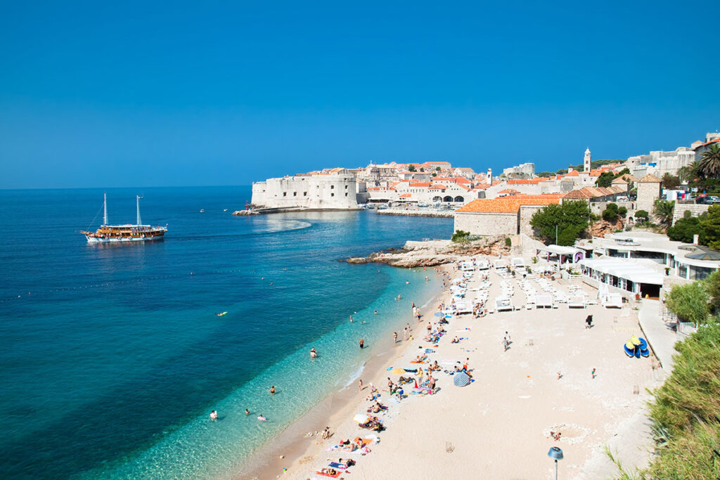 The tourists sunbathing on the pebble beach with the view on the old town of Dubrovnik.
