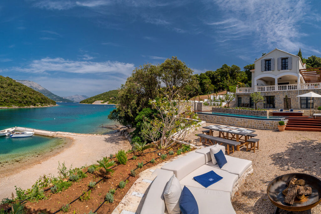 A white mediterranean villa on the seaside, inside the peaceful bay with crystally blue sea.