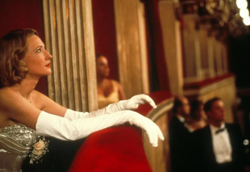 The woman in a golden dress, with white gloves watching opera from the balcony.