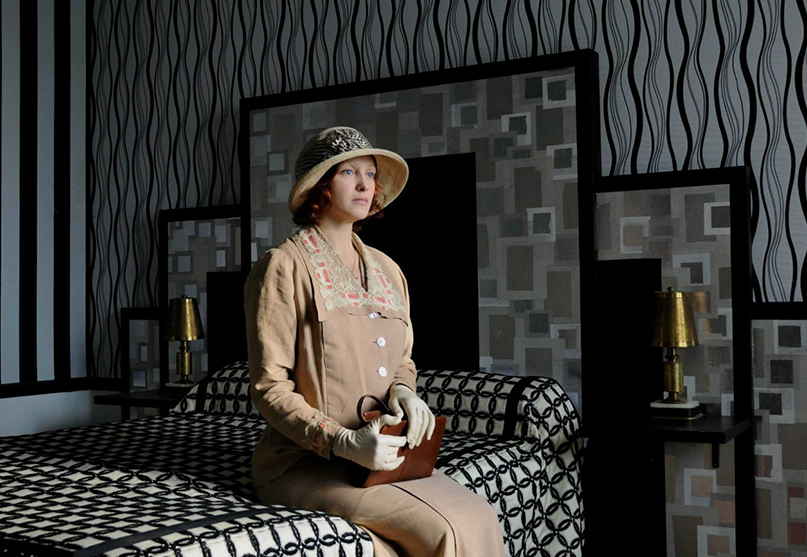 The woman in the brown dress and with a brown hat, sitting on the black bed, in art-deco, black coloured bedroom.