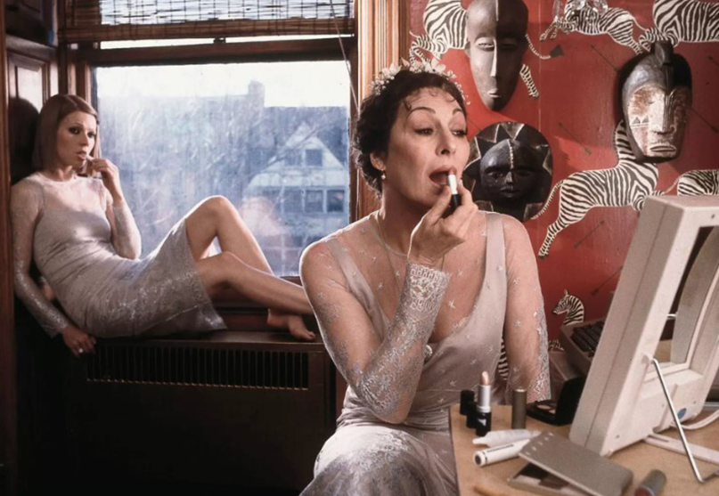Two women in the bedroom. The one on the right is fixing the make-up, while the other sits by the window.