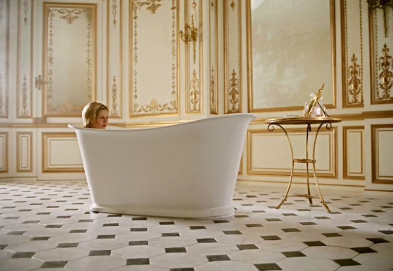 The woman in a white bathtub that stands on black and white mosaic floor.
