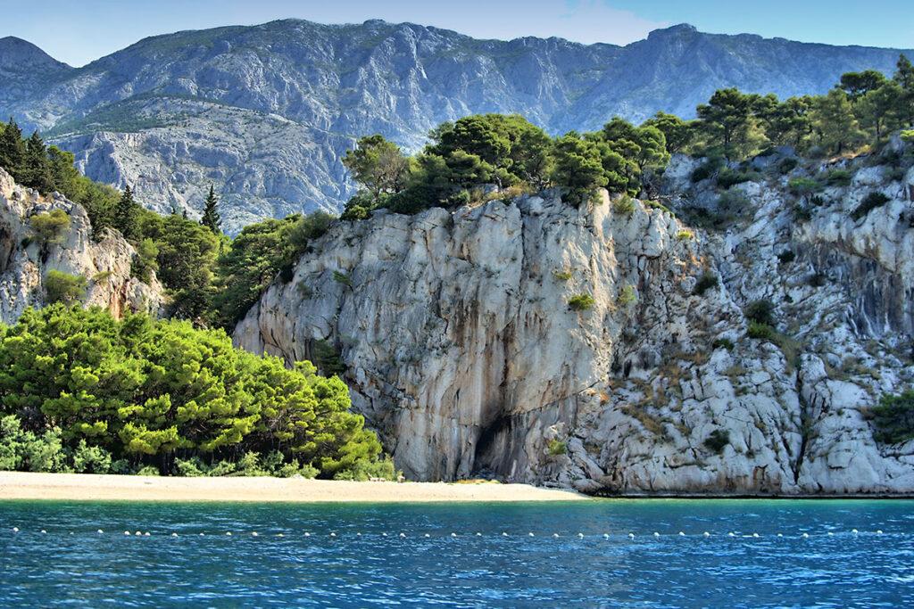 A small pebble beach under a huge rock.