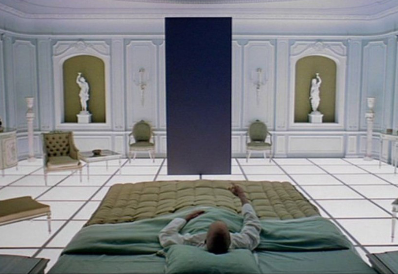 The man lying in the bed with olive-green sheets. The man is facing a black screen in the middle of the white presidential looking suite.