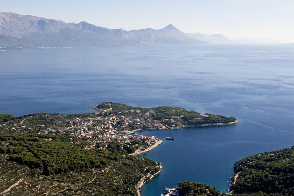 The seaside town positioned in a bay sheltered by a peninsula covered with pine trees.