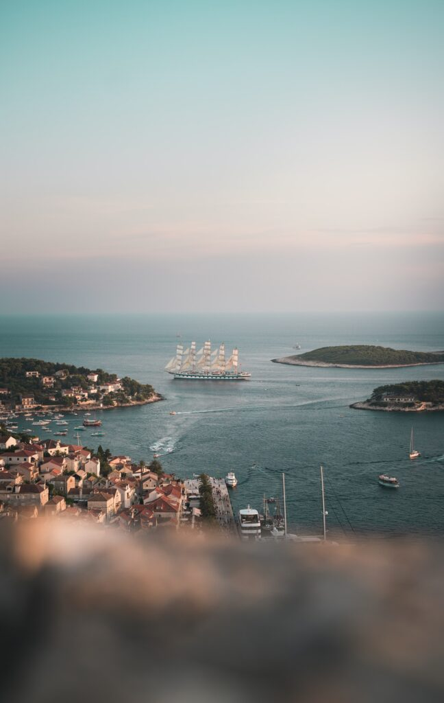 The panoramic view on the small Mediterranean town in the small bay. In the focus is a sailing ship and three small boats.