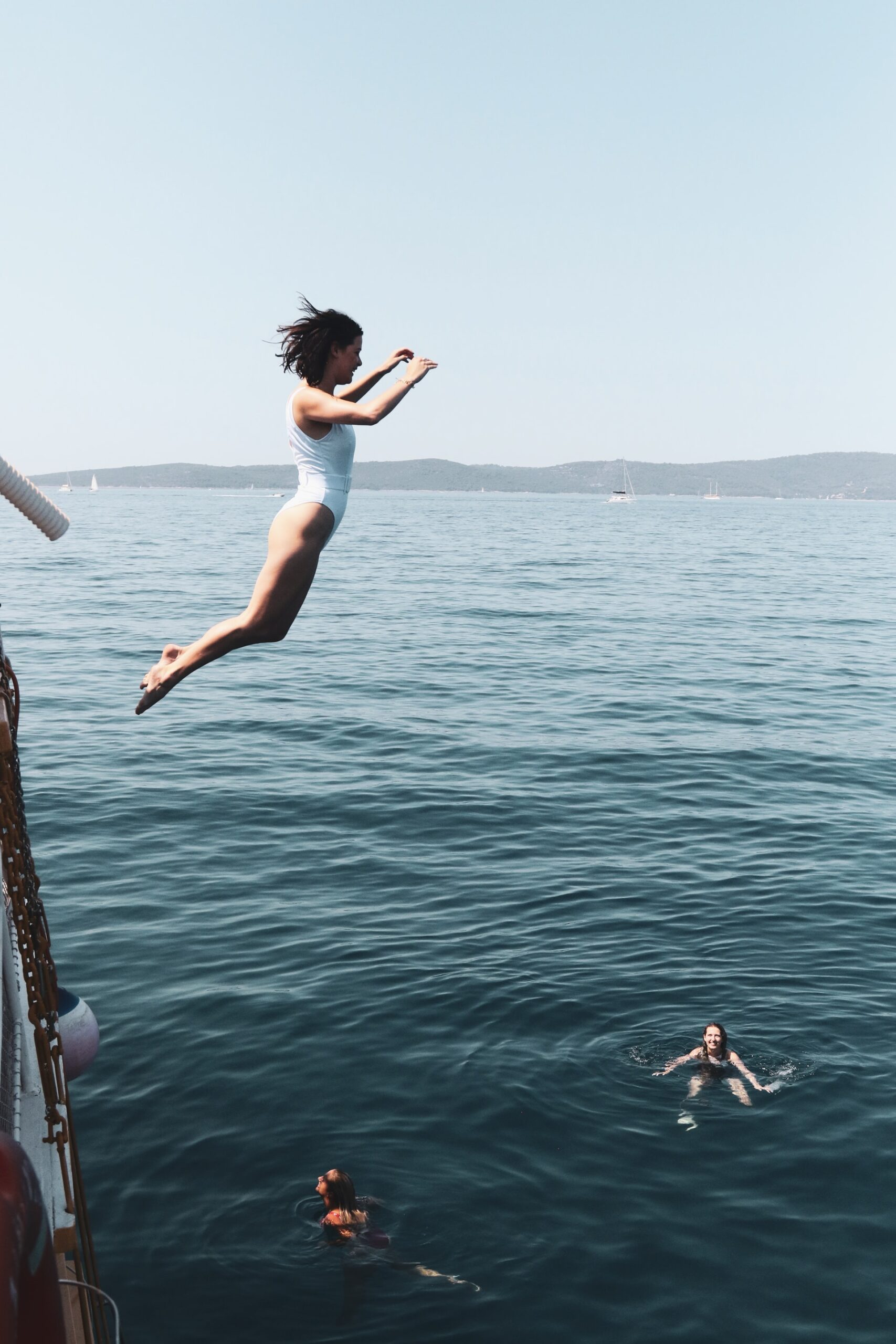 A woman jumping into the sea from a boat.